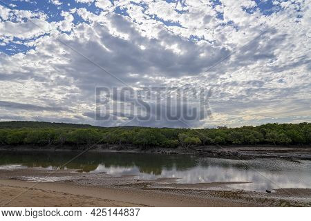 Creek At Low Tide With Mud And Sandbanks Visible And A Bushland Shoreline Under A Cloudy Blue Sky