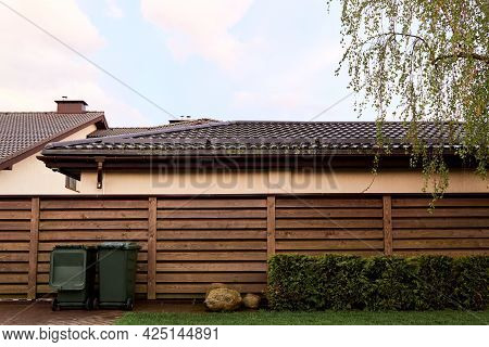 Side View Of One-story Private Country House With A Wooden Fence Made Of Horizontal Planks. Landscap