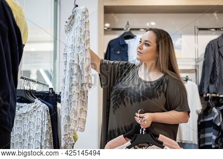 Stylish Plus Size Female Shopaholic Choosing Clothes At Store Boutique Buyer Enjoying Shopping