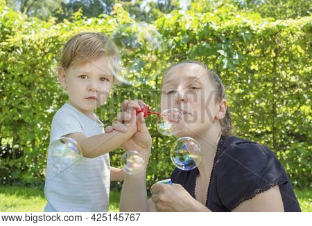 Cute Little Boy And His Mother Having Fun Blowing Soap Bubbles In The Park. Funny Outdoor Activity F