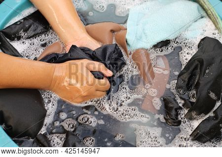 Woman's Hand Washing Colored Clothes In A Plastic Basin. Wash Clothes By Hand With Detergent. There
