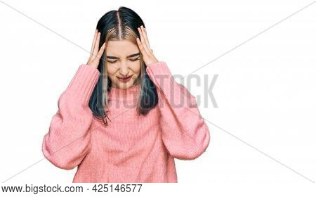 Young modern girl wearing pink wool winter sweater suffering from headache desperate and stressed because pain and migraine. hands on head.