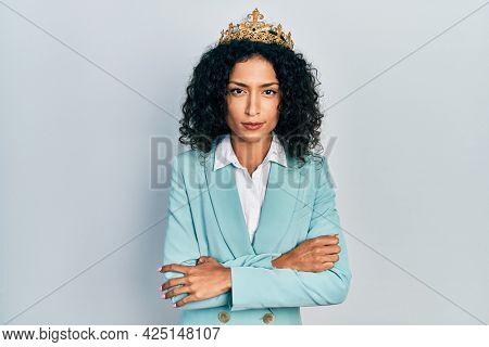 Young latin girl wearing business clothes and queen crown skeptic and nervous, disapproving expression on face with crossed arms. negative person.