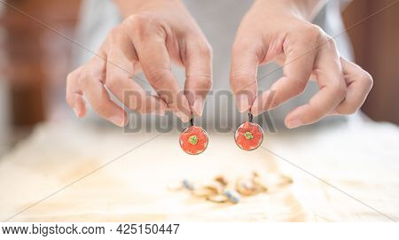 The Female Hands Holding  The Metal Plate Frame Earring For Flower Embroidery Thread On The White Co