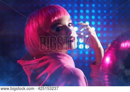 Disco style. Modern girl with bright glitter make-up and pink hair poses in the neon lights of the nightclub. Night party style.