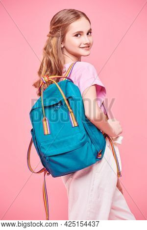 Portrait of a smiling pretty girl teenager in light summer clothes and with backpack posing at studio on a pink background. School time. Youth fashion.