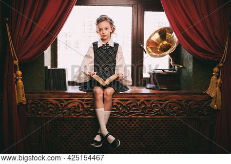 Cute eight year old girl in elegant classic school uniform sits in a luxurious vintage room and reads a book. Kid's school fashion.
