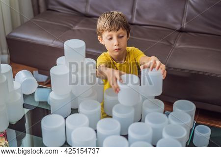 Boy Playing With Cans Of Yogurt Surrounded By Many Jars Of Yoghurt That He Uses In A Year. A Huge Am