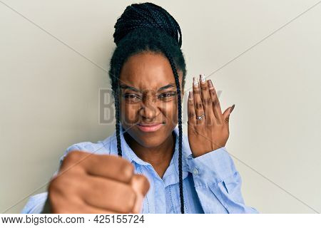 African american woman with braided hair wearing engagement ring annoyed and frustrated shouting with anger, yelling crazy with anger and hand raised