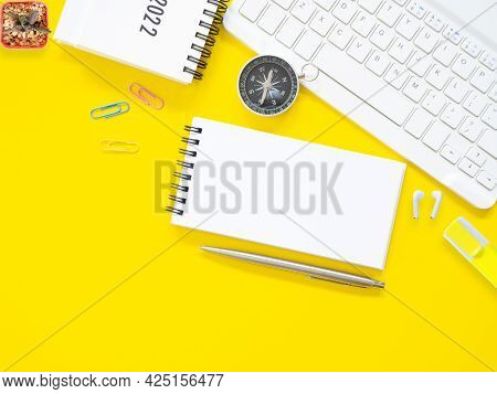 Top View, Flat Lay, Blank Notepad On Office Yellow Workplace Tabletop With Pen, Keyboard, Calendar,