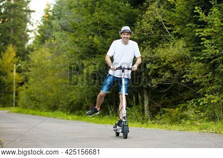 Electric Urban Transportation.young Handsome Man In White Shirt, Sunglasses And Hat Ready To Ride Hi
