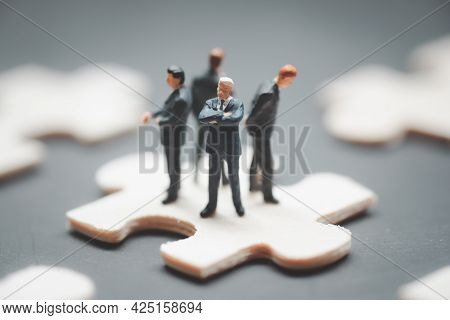 Four Miniature Businessman Standing Back To Back And Standing On Jigsaw Puzzle Piece. Business Suppo