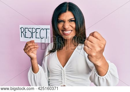 Young latin transsexual transgender woman holding respect message paper annoyed and frustrated shouting with anger, yelling crazy with anger and hand raised