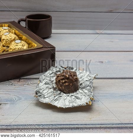 Chocolate Candy With Nuts Lies On A Plank Surface. The Foil Wrapper Is Unfolded. Next To It Is A Box