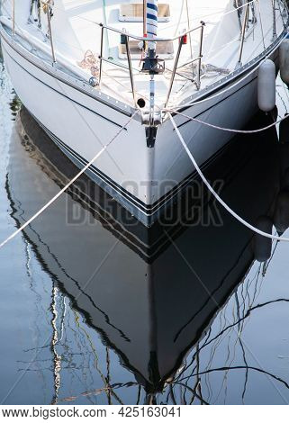 Boat hull at the port reflecting symmetrical in the water