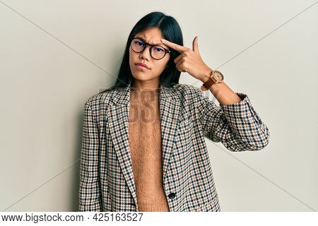 Young chinese woman wearing business style and glasses pointing unhappy to pimple on forehead, ugly infection of blackhead. acne and skin problem