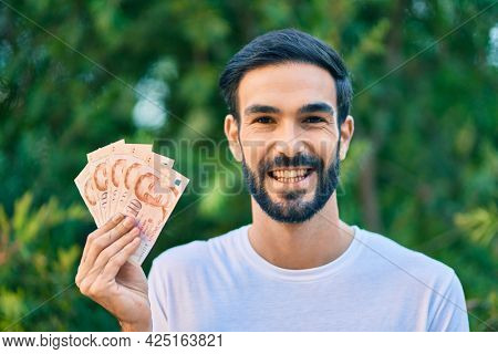 Young hispanic man smiling happy holding turkish lira banknotes at the park.