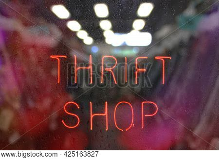 Vintage Neon Thrift Shop Sign In Wet Window