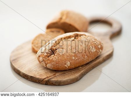 Homebaked hot appetizing bread with crispy crust sliced on wooden cutting board