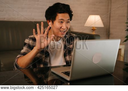 Young Asian Male Entrepreneur In Casual Clothing And Earphone Waving Hand While Starting Video Call