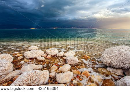 Rocky beach covered with evaporated salt. Gloomy sky with dark thunderclouds. Magnificent exotic resort for treatment and relaxation. Israeli coast. The Dead Sea is a closed salt lake.