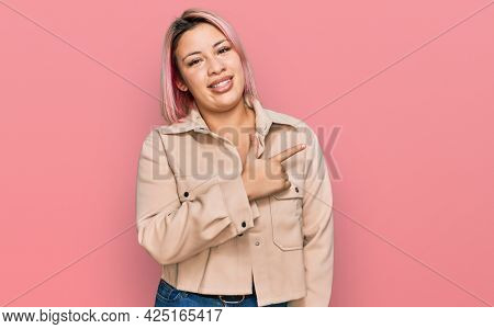 Hispanic woman with pink hair wearing casual clothes cheerful with a smile of face pointing with hand and finger up to the side with happy and natural expression on face
