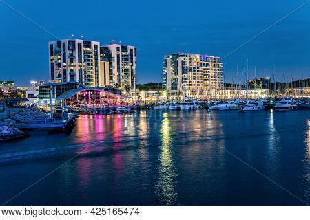 Marina is a harbor for yachts, boats and small boats in Herzliya, Israel. Evening twilight on the Mediterranean Sea. Walk along the breakwater that protects the yacht harbor from storms.
