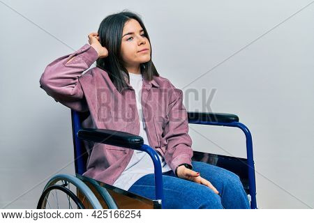 Young brunette woman sitting on wheelchair confuse and wondering about question. uncertain with doubt, thinking with hand on head. pensive concept.