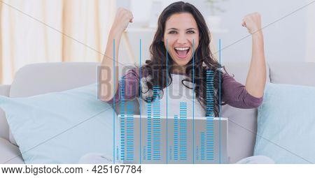 Composition of data processing over woman celebrating using laptop. global business, digital interface, technology and networking concept digitally generated image.