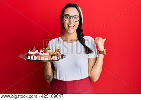 Young hispanic woman wearing waiter uniform holding cakes pointing thumb up to the side smiling happy with open mouth