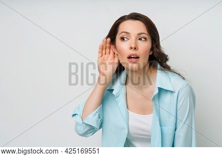 A Young Woman Eavesdrops On Someone Elses Conversation With Her Hand To Her Ear. The Concept Of Eave