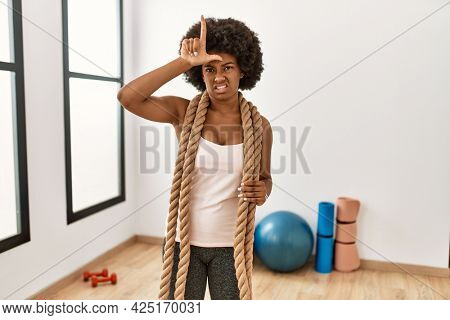 Young african american woman with afro hair at the gym training with battle ropes making fun of people with fingers on forehead doing loser gesture mocking and insulting.