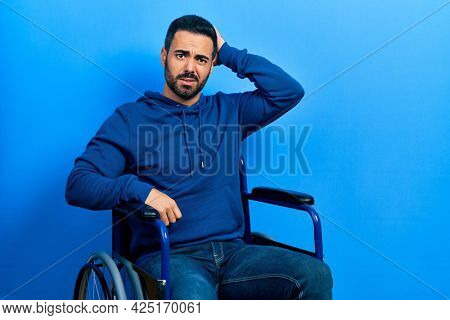 Handsome hispanic man with beard sitting on wheelchair confuse and wonder about question. uncertain with doubt, thinking with hand on head. pensive concept.