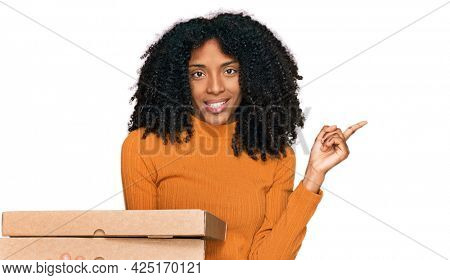 Young african american girl holding delivery pizza box smiling happy pointing with hand and finger to the side