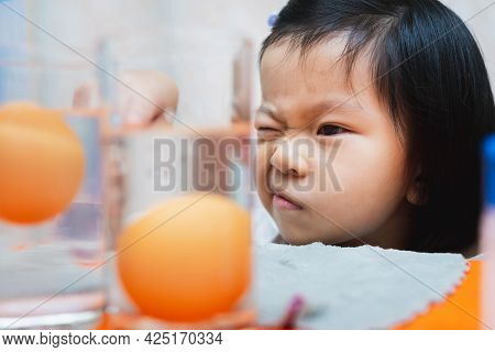 Head Shot. Asian Child Girl Is Observing Science Experiment On Sinking Eggs - Floating Eggs With Pla