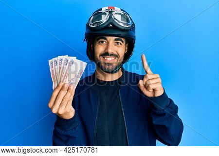 Young hispanic man wearing motorcycle helmet holding russian ruble smiling with an idea or question pointing finger with happy face, number one