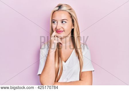 Young blonde girl wearing casual white t shirt thinking concentrated about doubt with finger on chin and looking up wondering