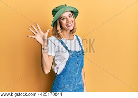 Young caucasian blonde woman wearing denim jumpsuit and hat with 90s style showing and pointing up with fingers number five while smiling confident and happy.