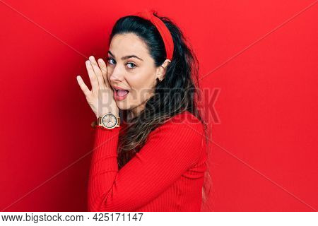Young hispanic woman wearing casual clothes hand on mouth telling secret rumor, whispering malicious talk conversation