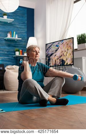 Senior Woman In Sportwear Warming Up Arm Muscles Practicing Wellness Workout Using Dumbbells. Pensio