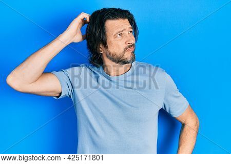 Middle age caucasian man wearing casual clothes confuse and wondering about question. uncertain with doubt, thinking with hand on head. pensive concept.