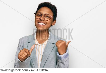 Young african american woman wearing business clothes pointing to the back behind with hand and thumbs up, smiling confident