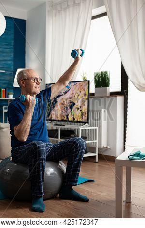 Retirement Senior Man Sitting On Aerobics Swiss Ball Raising Hand Streching Arm Muscle Doing Fitness