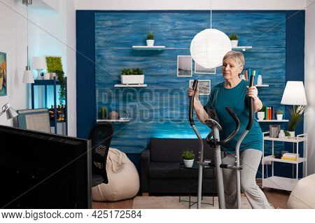 Focused Senior Woman Working At Legs Muscle Resistance Cycling Bicycle Machine In Living Room During