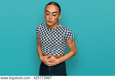 Hispanic transgender man wearing make up and long hair wearing modern clothes with hand on stomach because indigestion, painful illness feeling unwell. ache concept.