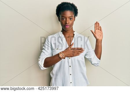 Young african american girl wearing casual clothes swearing with hand on chest and open palm, making a loyalty promise oath