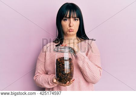 Young hispanic woman holding jar of raisins depressed and worry for distress, crying angry and afraid. sad expression.