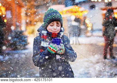 Little Cute Kid Boy Drinking Hot Children Punch Or Chocolate On German Christmas Market. Happy Child