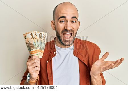 Young hispanic man holding 500 norwegian krone banknotes celebrating achievement with happy smile and winner expression with raised hand