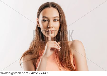 Shh Gesture. Young Beautiful Serious Girl Holding A Finger To Her Lips On A White Isolated Backgroun